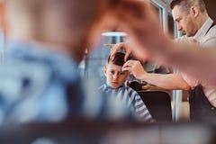 Pouco menino de escola bonito teve seu primeiro corte de cabelo na moda no barbeiro moderno fotos de stock royalty free