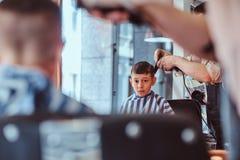 Pouco menino de escola bonito teve seu primeiro corte de cabelo na moda no barbeiro moderno foto de stock
