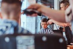 Pouco menino de escola bonito teve seu primeiro corte de cabelo na moda no barbeiro moderno fotos de stock