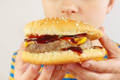 Pouco menino engraçado com um Hamburger saboroso no fim branco do fundo acima fotos de stock