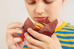 Pouco menino engraçado com um queque saboroso da maçã no fim branco do fundo acima imagens de stock royalty free