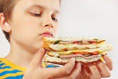 Pouco menino engraçado com um sanduíche saboroso no fim branco do fundo acima fotos de stock