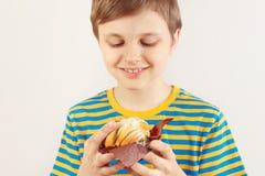 Pouco menino engraçado em uma camisa listrada com o bolo de maçã no fundo branco imagens de stock royalty free