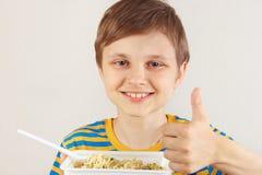Pouco menino engraçado em uma camisa listrada recomenda macarronetes imediatos no fundo branco imagem de stock royalty free