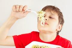 Pouco menino engraçado em uma camisa vermelha com os macarronetes imediatos no fundo branco foto de stock royalty free