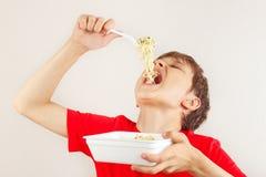 Pouco menino engraçado em uma camisa vermelha que come macarronetes imediatos no fundo branco imagens de stock royalty free