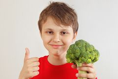 Pouco menino engraçado em uma camisa vermelha recomenda brócolis frescos no fundo branco imagem de stock royalty free