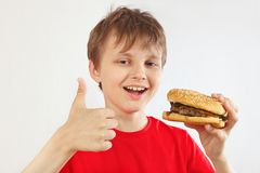 Pouco menino engraçado em uma camisa vermelha recomenda e gosta do Hamburger saboroso no fundo branco foto de stock