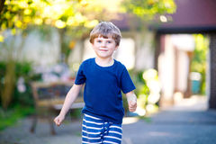 Pouco menino engraçado louro da criança que joga amarelinha no campo de jogos fora Imagem de Stock