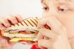 Pouco menino engraçado que come um sanduíche saboroso no fim branco do fundo acima foto de stock royalty free