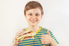 Pouco menino engraçado recomenda e gosta do sanduíche dobro no fundo branco imagens de stock royalty free