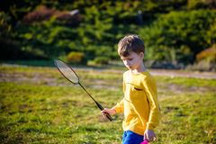 Pouco menino engra?ado bonito da crian?a com a raquete de badminton que joga no parque no dia de mola morno do ver?o Do Active jo foto de stock royalty free