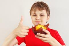 Pouco menino engra?ado em uma camisa vermelha recomenda o queque no fundo branco fotos de stock royalty free