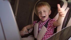 Pouco menino feliz está sentando-se em um banco de carro da criança em um carro e mostra seu polegar acima video estoque