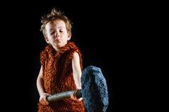 Pouco menino irritado engraçado do guerreiro Neanderthal ou uma CTOC-Magnon Homem das cavernas antigo, selvagem masculino imagens de stock royalty free