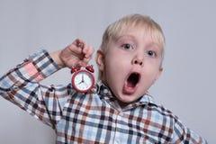 Pouco menino louro com um despertador vermelho em suas m?os Cara surpreendida Conceito da manh? Fundo claro imagem de stock royalty free