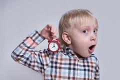 Pouco menino louro com um despertador vermelho em suas m?os Cara surpreendida Conceito da manh? Fundo claro imagem de stock