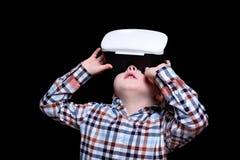 Pouco menino louro com vidros da realidade virtual olha acima Camisa de manta Fundo preto fotografia de stock