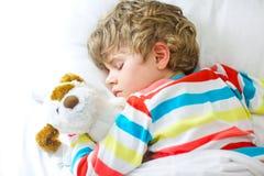 Pouco menino louro da criança no nightwear colorido veste o sono fotografia de stock