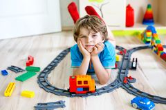 Pouco menino louro da criança que joga com blocos coloridos do plástico e que cria o estação de caminhos-de-ferro Fotografia de Stock Royalty Free