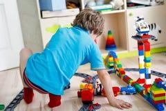 Pouco menino louro da criança que joga com blocos coloridos do plástico e que cria o estação de caminhos-de-ferro Fotos de Stock