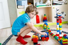 Pouco menino louro da criança que joga com blocos coloridos do plástico e que cria o estação de caminhos-de-ferro Imagem de Stock Royalty Free