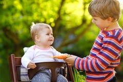 Pouco menino louro da crian?a que d? uma cenoura ? irm? do beb? Irm?os felizes que comem o petisco saud?vel Beb? que senta-se no  foto de stock