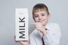 Pouco menino louro guarda e mostra o indicador em um grande pacote branco do leite da caixa camisa branca e la?o vermelho Fundo c foto de stock royalty free