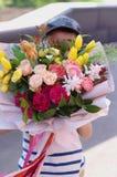 Pouco posição de sorriso do menino com um ramalhete da flor Flores bonitas para a mãe fotos de stock