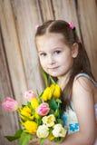 Pouco ramalhete bonito da terra arrendada da menina das tulipas fotografia de stock