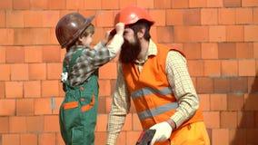Pouco trabalhador do filho que erige uma parede de tijolo Filho no capacete de seguran?a que ajuda seu pai Casa da construção do  vídeos de arquivo