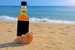 Pouco uísque da garrafa nos escudos do oceano está na areia Partido alcoólico em um estilo náutico nas costas do Atlântico foto de stock royalty free