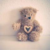 Pouco urso de peluche senta-se para baixo com cookie do coração Imagem de Stock