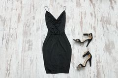 Pouco vestido e sapatas pretos Fundo de madeira, engodo elegante Imagem de Stock Royalty Free