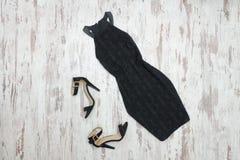 Pouco vestido e sapatas pretos Fundo de madeira, engodo elegante imagem de stock