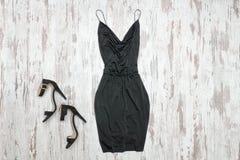 Pouco vestido e sapatas pretos Fundo de madeira, engodo elegante Fotografia de Stock Royalty Free