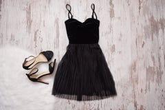 Pouco vestido preto e sapatas pretas Fundo de madeira, conceito elegante Fotografia de Stock Royalty Free