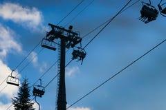 Poucos esquiam telecadeira com o céu azul nebuloso bonito no fundo imagens de stock