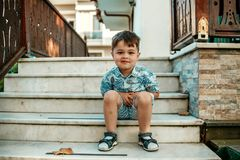 Poucos l e menino muito bonito que sentam-se nas escadas e no sorriso fotos de stock royalty free