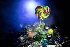 Poucos pirulitos coloridos do coração dos doces em doces coloridos diferentes contra o fundo nevoento tonificado escuro Fotografia de Stock Royalty Free