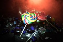 Poucos pirulitos coloridos do coração dos doces em doces coloridos diferentes contra o fundo nevoento tonificado escuro Imagens de Stock Royalty Free