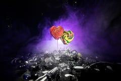 Poucos pirulitos coloridos do coração dos doces em doces coloridos diferentes contra o fundo nevoento tonificado escuro Imagem de Stock
