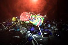 Poucos pirulitos coloridos do coração dos doces em doces coloridos diferentes contra o fundo nevoento tonificado escuro Imagens de Stock