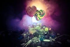 Poucos pirulitos coloridos do coração dos doces em doces coloridos diferentes contra o fundo nevoento tonificado escuro Foto de Stock