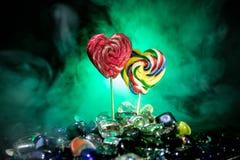 Poucos pirulitos coloridos do coração dos doces em doces coloridos diferentes contra o fundo nevoento tonificado escuro Fotos de Stock Royalty Free