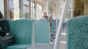 Poucos povos não reconhecidos montam em um trem do metro ou do bonde Vista da parte traseira Movimento lento video estoque