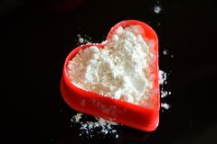 Poudre blanche sur l'amour rouge de coeur Images stock