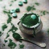 Poudre d'algues vert moulu de spirulina de concept de Superfood, comprimés de pilules photos libres de droits