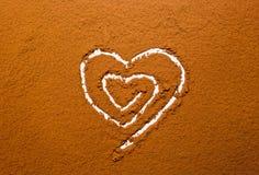 Poudre de cacao de coeur Photographie stock