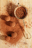 Poudre de cacao de truffes de chocolat époussetée et passoir Photographie stock